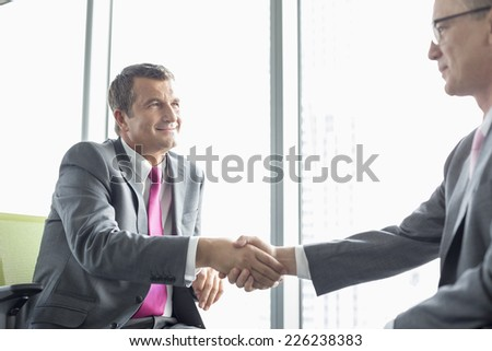 Mature businessmen shaking hands in office - stock photo