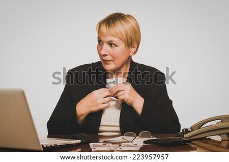 Mature businesswoman hides money.  - stock photo