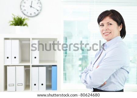 Mature businesswoman looking at camera in office - stock photo