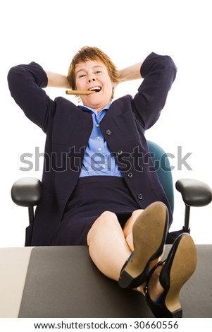 Mature businesswoman smoking a cigar with her feet on her desk.  Isolated on white. - stock photo
