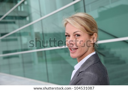 Mature businesswoman standing in front of modern building - stock photo