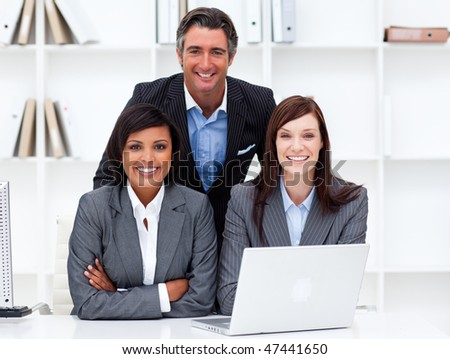 Mature businesswomen and their colleague working at a laptop in the office - stock photo