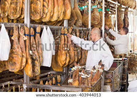 Mature butcher and his young assistant with jamon joints at a meat factory  - stock photo