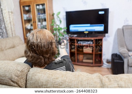 Mature Caucasian woman pushing tv remote control - stock photo
