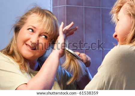 mature caucasian woman struggling to brush out her tangled hair in mirror - stock photo