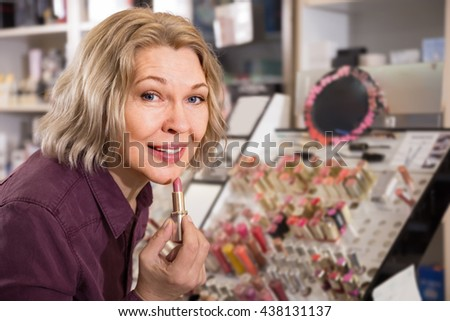 mature charming woman choosing lip plumper on display and smiling - stock photo
