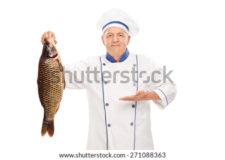 Mature chef holding a big freshwater fish and gesturing with his hand isolated on white background - stock photo