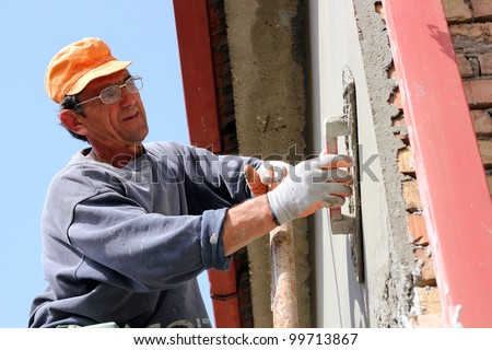 Mature contractor plasterer working outdoors. - stock photo