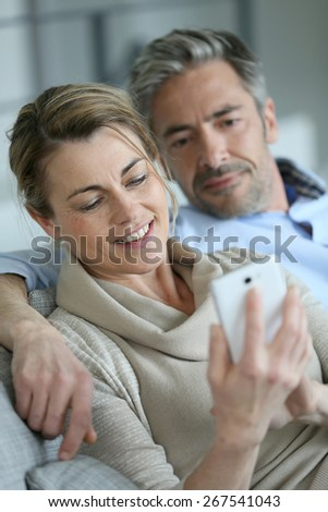 Mature coupel sitting in sofa and using smartphone - stock photo