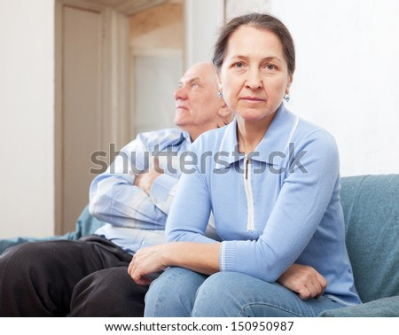Mature couple after quarrel in living room at home  - stock photo