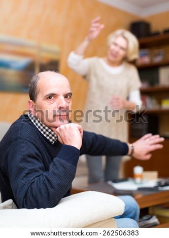 Mature couple are having a conflict in living room. Fed up senior husband is showing her wife to stop yelling at him - stock photo