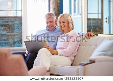 Mature Couple At Home In Lounge Using Laptop Computer - stock photo