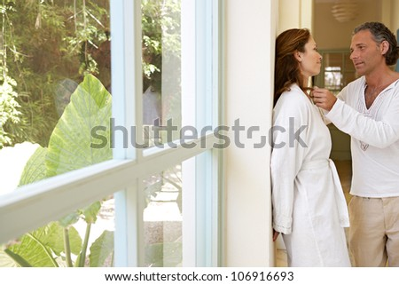 Mature couple being romantic by a garden's corridor, at home. - stock photo