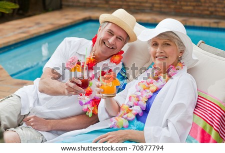 Mature couple drinking a cocktail  beside the swimming pool - stock photo