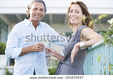 Mature couple drinking champagne while leaning on a hotel's balcony outdoors, smiling at camera. - stock photo