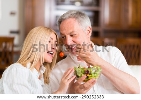 Mature couple eating a salad in the living room - stock photo