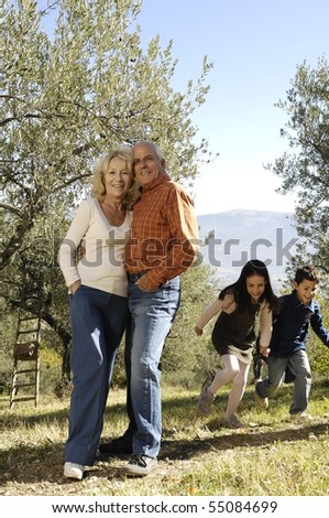 mature couple embracing while kids are running - stock photo