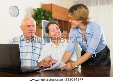 Mature couple filling questionnaire for employee with laptop of the bank - stock photo
