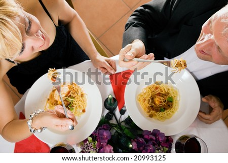 Mature couple having a romantic dinner looking at each other while eating - stock photo