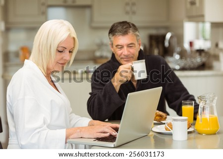 Mature couple having breakfast together woman using laptop at home in the kitchen - stock photo