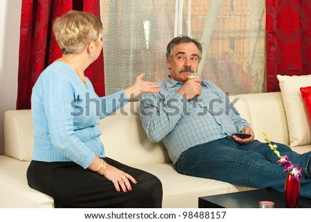 Mature couple having conflict in their house  and the man drinking beer and listening wife - stock photo
