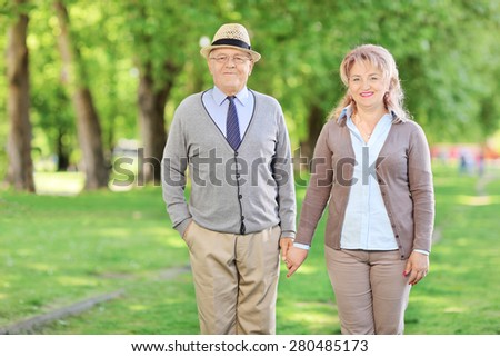 Mature couple holding hands and posing in a park on a sunny summer day - stock photo
