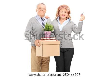 Mature couple holding moving boxes and keys isolated on white background - stock photo