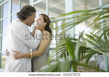 Mature couple hugging at home, standing by large garden doors and surrounded by foliage. - stock photo