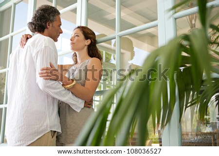 Mature couple hugging in a home terrace with large french doors. - stock photo