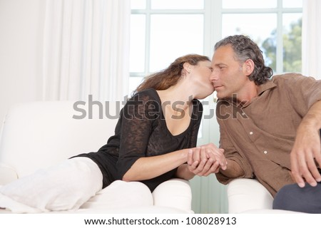 Mature couple kissing while lounging on a white sofa at home. - stock photo