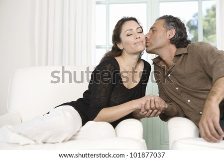 Mature couple kissing while sitting by large garden doors in living room. - stock photo