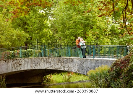 Mature couple leaning on railing of bridge resting during stroll in park - stock photo