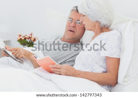 Mature couple looking at a newspaper in bed - stock photo