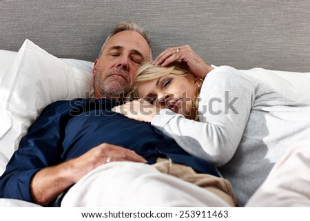 Mature couple lying on bed together sleeping  - stock photo