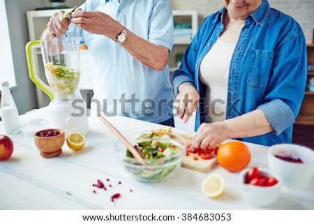Mature couple preparing a meal together in the kitchen - stock photo