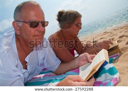 Mature couple reading, relaxing on tropical beach. The sky is blue with clouds in the background. - stock photo