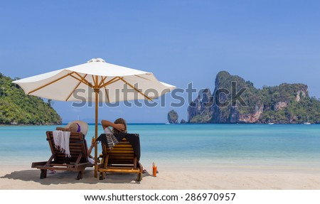 Mature couple relaxing on the beach in Thailand - stock photo