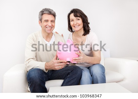 Mature couple saving money in piggybank at home - stock photo