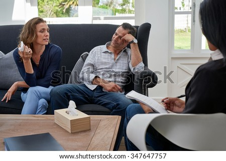mature couple seated on couch, woman crying during therapy session - stock photo