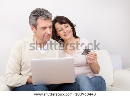 Mature couple shopping in internet using laptop at home - stock photo