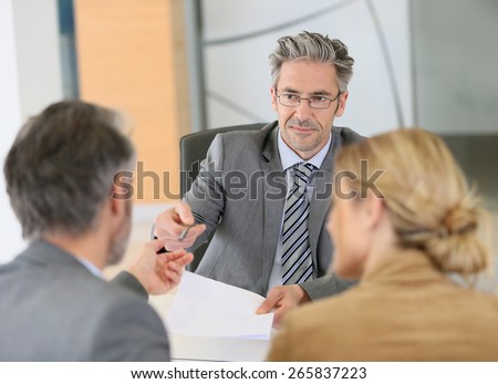 Mature couple signing contract in lawyer's office - stock photo