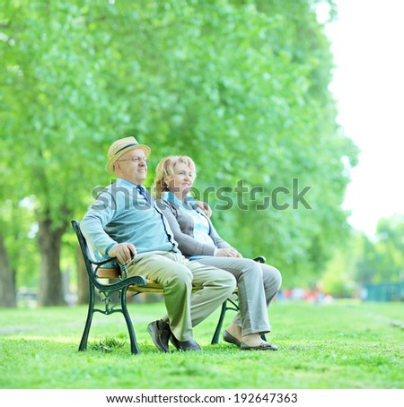 Mature couple sitting on a bench in park and relaxing shot with a tilt and shift lens - stock photo