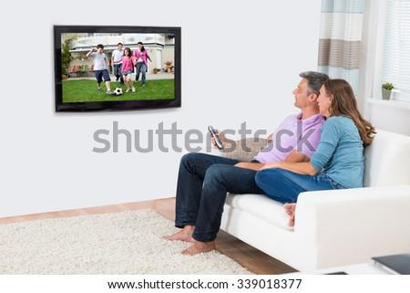 Mature Couple Sitting On Sofa And Enjoying Watching Television - stock photo