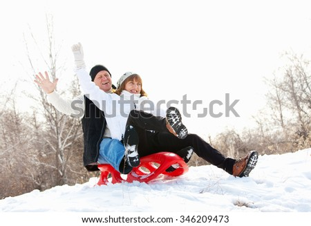 Mature couple sledding. Seniors couple on sled in winter park - stock photo