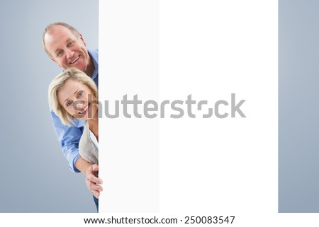 Mature couple smiling behind wall against grey vignette - stock photo