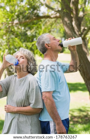 Mature couple standing and drinking water at the park - stock photo