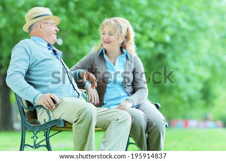 Mature couple talking seated on bench in park - stock photo