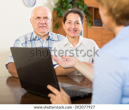 Mature couple talking with employee with laptop at home - stock photo