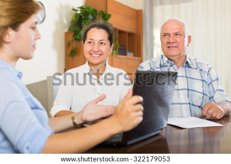 Mature couple talking with employee with laptop at home. Focus on woman - stock photo