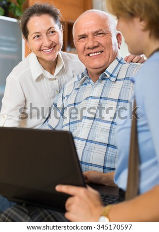 Mature couple talking with social worker with laptop at home and smiling. Focus on man